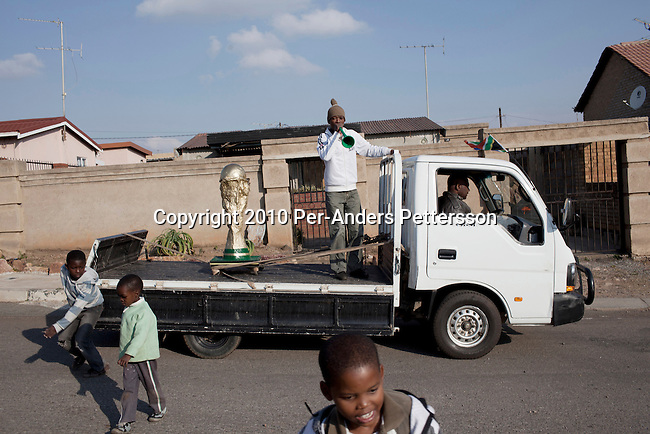 JOHANNESBURG, SOUTH AFRICA - JUNE 11: A man drives a truck with a homemade World Cup Trophy on on June 11, 2010 in Vilakazi street, in Orlando Soweto, in South South Africa. Locals and visitors come out in the street celebrating the start of the World Cup tournament. South Africa played Mexico in the opening game and the final score was 1-1. South Africa didn't advance past the group stage in the 2010 World Cup, held in their own country. In hosting the largest sporting event in the world, South Africa has a chance to impress the world with their country, hoping that the month long event will bring long lasting benefits for the country. (Photo by Per-Anders Pettersson)