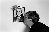 Albania. Tirana. The man is a professional musician and a member of the Orchestra Frymore which is the only Albanian military brass band. He kisses at home the portrait of his beloved deceased mother. The Orchestra Frymore is the only Albanian military brass band. Tirana is the capital and largest city of Republic of Albania. 26.11.1998 © 1998 Didier Ruef