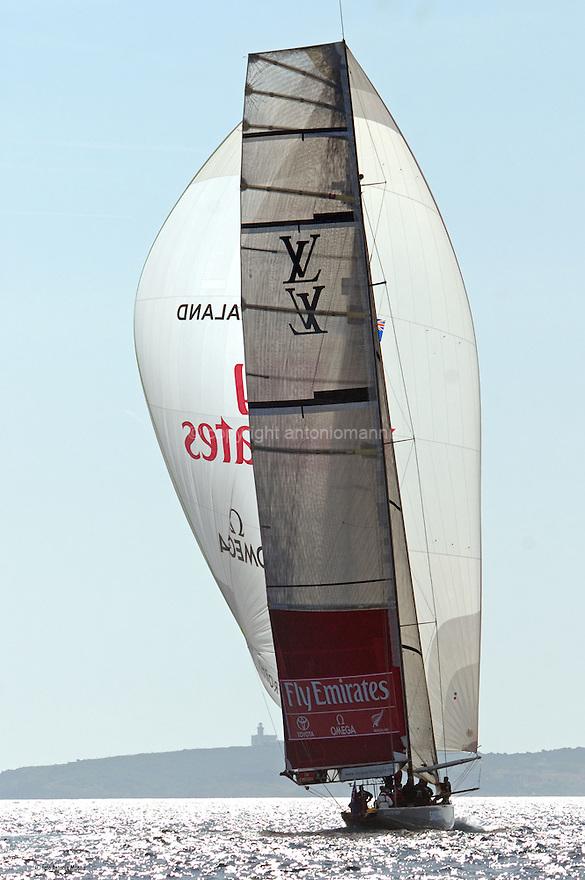 Louis Vuitton Trophy La Maddalena 30 maggio 2010. Emirates Team New Zealand naviga sotto spi nel corso di una regata con gli statunitensi di Oracle. Sullo sfondo il faro di Capo Ferro.