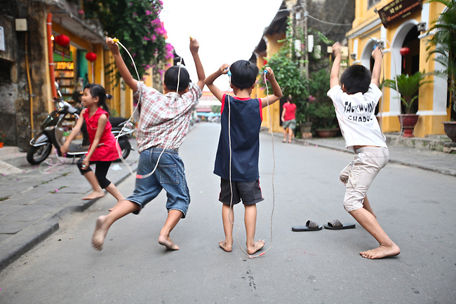 Boys playing jump rope prepare to race each other down a street one late afternoon in Hoi An, Vietnam. April 22, 2012.