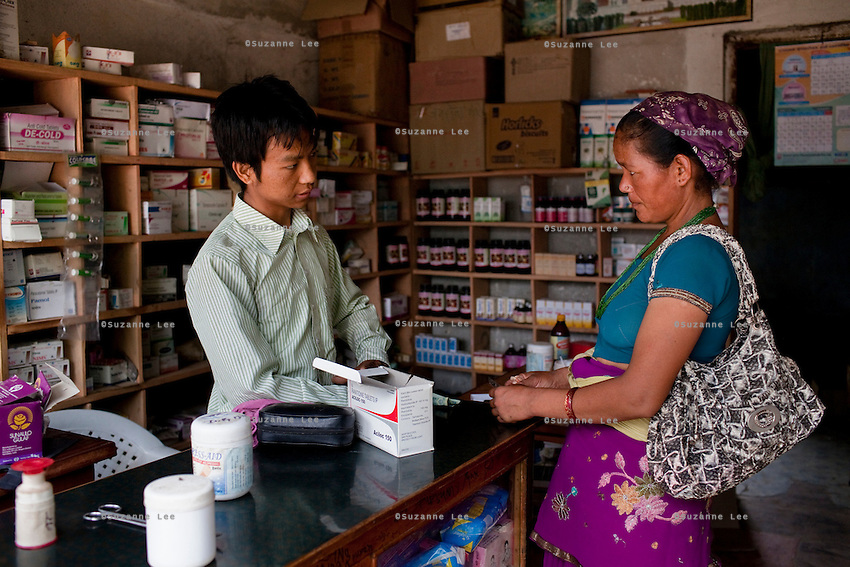 Rana Bahadur Magar (left), 24, attends to a customer in his pharmacy which he bought over 2 years ago in Gangate Village, Sathakhani Bidishi, Surkhet district, Western Nepal, on 30th June 2012. Monthly, Rana Bahadur Magar sells over 300 condoms and 1700 birth control pills and does about 10 injections of 3-month-long contraceptives which he is trained to do. The nearest district hospital is an hour's drive away. In Surkhet, StC partners with Safer Society, a local NGO which advocates for child rights and against child marriage.  Photo by Suzanne Lee for Save The Children UK