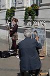 Street artist painting woman busker, Norwich, England