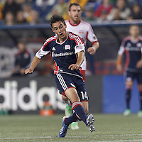 New England Revolution midfielder Diego Fagundez (14) follows through on a shot. In a Major League Soccer (MLS) match, the New England Revolution (blue) tied New York Red Bulls (white), 1-1, at Gillette Stadium on May 11, 2013.