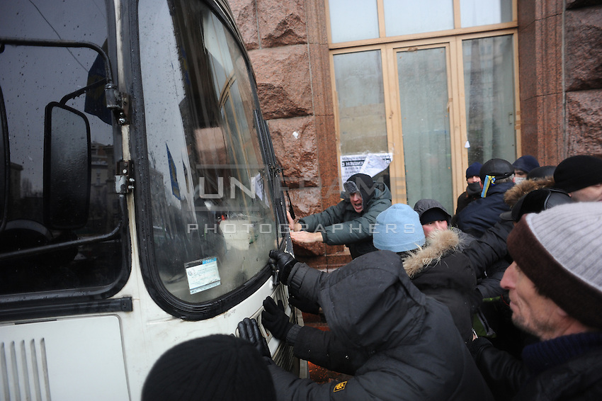 Protesters push away busses of the Berkut special police force during failed assault on town hall. Kiev Ukraine.   The temperature on the street is 12 degrees C. below zero<br /> <br /> Berkut special police forces have frozen water on their uniforms after they have being sprayed with fire hydrants by the protesters in the  town hall. Kiev Ukraine.   The temperature on the street is 12 degrees C. below zero<br /> <br /> Protesters did not give up after the faint  attempt of evacuation performed by the police of the night before. Despite the adverse weather conditions,  they restored and rebuilt the complex structures of the  barricades under the snow in Maidan square. Kiev,  Ukraine.
