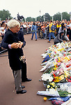 DEATH OF DIANA PRINCESS OF WALES 1997. london A CRYING WOMAN IS HUGGED BY A MAN AS THEY STAND IN FRONT OF A LARGE PILE OF FLORAL TRIBUTES TO PRINCESS DIANA AT BUCKINGHAM PALACE, BEHIND THEM MANY PEOPLE ARE QUEUEING THROUGH SHORT METAL FENCES.