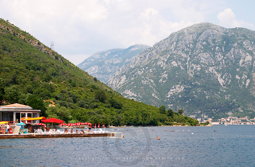 The narrow straight between Kamenari and Lepetani, view towards Perast and an impressive mountain top falling down to the sea bay Kotorski. A beach cafe with colourful sun shade umbrellas in Kamenari. Montenegro, Balkan, Europe.