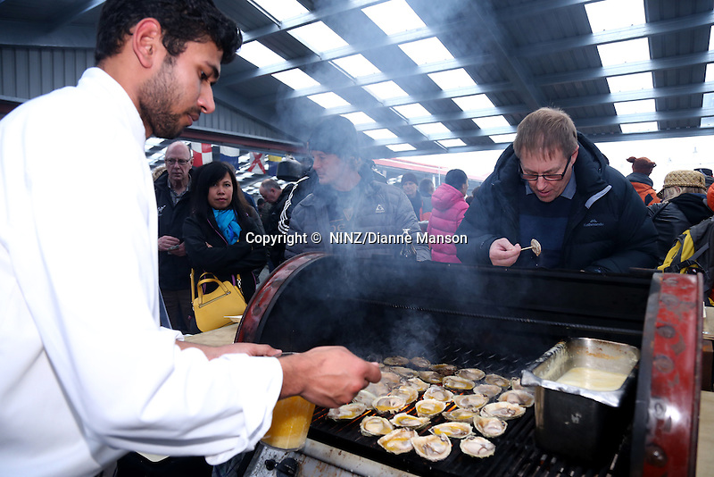 Vish Singh from the Ascot Hotel Emberz food stall cooks  barbequed Bluff oysters with garlic butter at the Bluff Oyster and Food Festival, Bluff, New Zealand, Saturday, May 21, 2016. Credit:  Dianne Manson