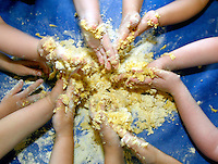 Children using their hands to mix baking ingredients