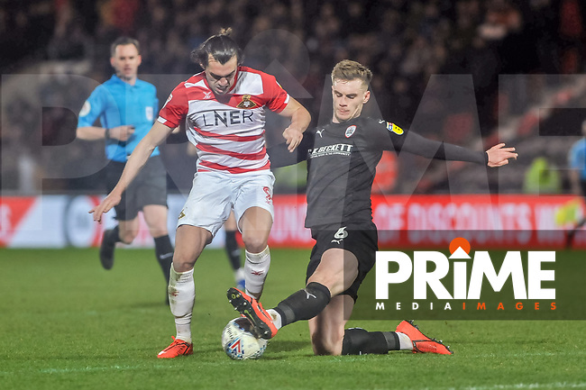 Barnsley's defender Liam Lindsay (6) tackles Doncaster Rovers forward John Marquis (9) during the Sky Bet League 1 match between Doncaster Rovers and Barnsley at the Keepmoat Stadium, Doncaster, England on 15 March 2019. Photo by Stephen Buckley / PRiME Media Images.