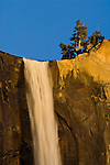 Water rushing over stone cliff at sunset in spring, Bridalveil Fall, Yosemite Valley, Yosemite National Park, California
