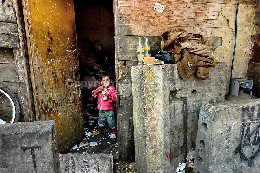 A little Colombian boy eats yoghurt in the 'Invasión', a temporary slum in Bogota, Colombia, 1 April 2006. The internal armed conflict in Colombia together with lack of social network caused appearence of small invasion slums in all Colombian urban zones in last years. These illegal settlements rise quickly in free uncontrolled spaces between industrial buildings, both in the city centres and peripheries. Shacks do not have sanitation network, neither electricity. Most of their inhabitants are war fugitives violently displaced from their original lands in the country by guerrilla or paramilitary forces. Picking up the rubbish and recycling it is a common survive strategy for people living in these temporal ghettos until those are not dismantled by city administration.