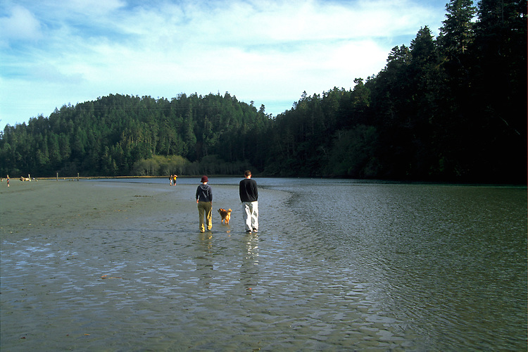 Young couple walking along the Big River estuary near Mendocino California
