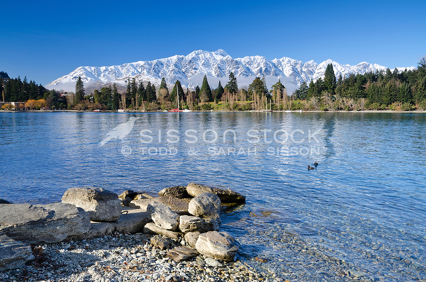 Rock foreground and Lake Wakatipu with Queenstown Gardens and the Remarkables Mountains in the background, South Island, New Zealand