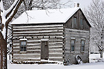 A historic log cabin during a winter season in Wisconsin