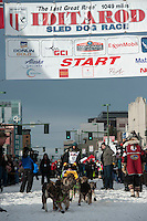Nicolas Petit and team leave the ceremonial start line with an Iditarider at 4th Avenue and D Street in downtown Anchorage, Alaska on Saturday, March 5th during the 2016 Iditarod race. Photo by Joshua Borough/SchultzPhoto.com
