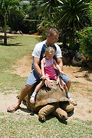MUS, Mauritius, bei Rivière des Anguilles, La Vanille Crocodile Park & Nature Reserve: Vater und Tochter reiten auf einer Riesenschildkroete | MUS, Mauritius, near Rivière des Anguilles, La Vanille Crocodile Park & Nature Reserve: father and daughter riding a giant turtle