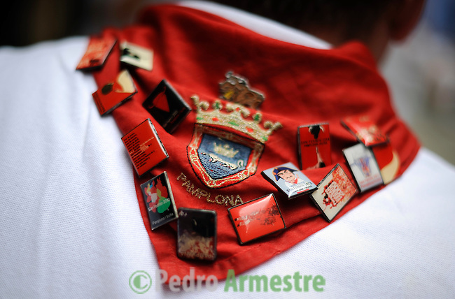 A man wears a red scarf full of pins during the San Fermin festival, on July 10, 2012, in the Northern Spanish city of Pamplona. The festival is a symbol of Spanish culture that attracts thousands of tourists to watch the bull runs despite heavy condemnation from animal rights groups. (c) Pedro ARMESTRE
