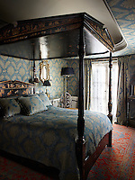 The bedroom has an intimate, luxurious ambience with a sumptuous four-poster bed at its centre. The decoration of the room is enlivened with laquer and touches of gilt.