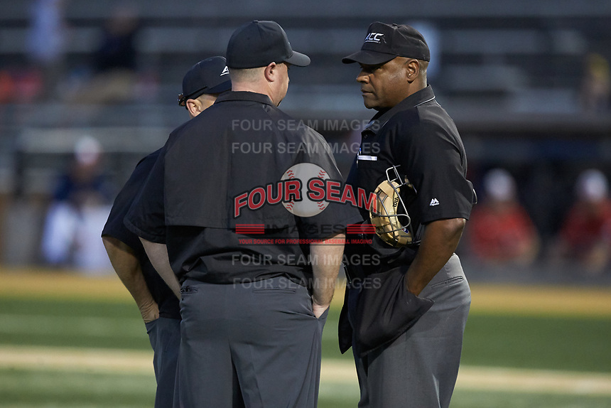 Home plate umpire Gregory Street (right) confers with third base umpire Brad Newton (center) and first base umpire Joseph Holt during the NCAA baseball game between the Liberty Flames and the Wake Forest Demon Deacons at David F. Couch Ballpark on April 25, 2018 in  Winston-Salem, North Carolina.  The Demon Deacons defeated the Flames 8-7.  (Brian Westerholt/Four Seam Images)