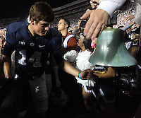 State College, PA - 10/12/2013:  PSU QB Christian Hackenberg rings the victory bell after the game.  Hackenberg was 23 for 44 passing for 305 yards and 3 touchdowns.  Penn State defeated Michigan by a score of 43-40 in four overtimes on Saturday, October 12, 2013, at Beaver Stadium.<br /> <br /> Photos by Joe Rokita / JoeRokita.com