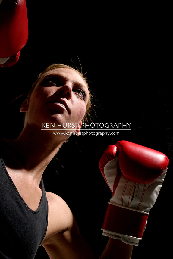 Young attractive blonde woman boxing.
