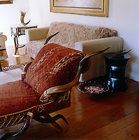 An antique chaise longue embellished with horn is the centrepiece of this living room