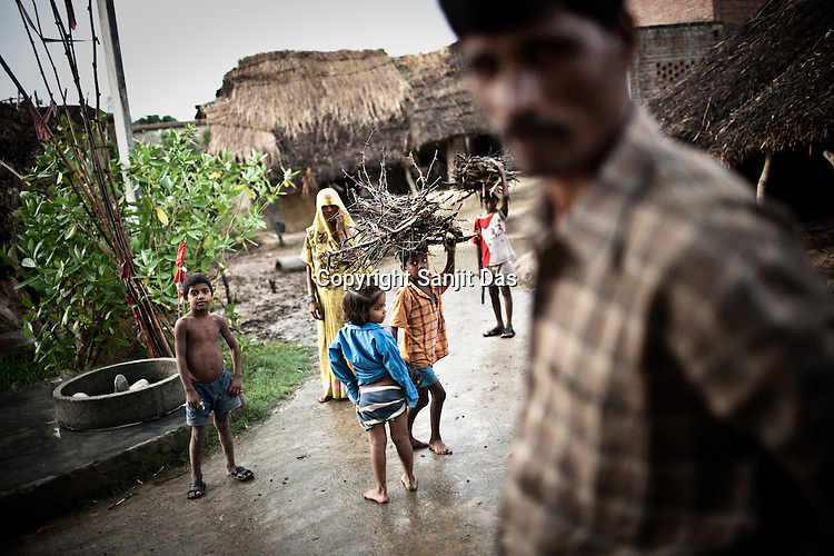 Children are seen carrying firewood in rain in Village Rajagaon in Block Machreta of Uttar Pradesh, India. The 4 month annual rainfall is crucial to summer sown crops as 60% of the farmlands are rainfed. North India experienced scanty rainfall in late june to july. Till August, rain in India has been 26% below 5 year average. Late rains moist the fields but it is not enough for rice, sugarcane, oilseeds and pulses. Late rains also damage the alternate crops that need less water.
