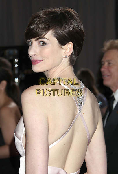 Anne Hathaway (wearing Prada).85th Annual Academy Awards held at the Dolby Theatre at Hollywood & Highland Center, Hollywood, California, USA..February 24th, 2013.oscars half length pink silk satin dress backless straps jewel encrusted embellished looking over shoulder back behind rear.CAP/ADM/RE.©Russ Elliot/AdMedia/Capital Pictures.