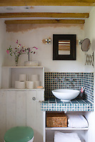In this bathroom tongue-and-groove, exposed beams and mosaic tiling have been used to create a pleasingly rustic effect