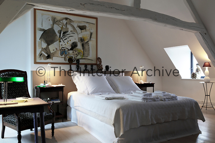 A double bed is positioned beneath a massive white-painted beam in this attic bedroom