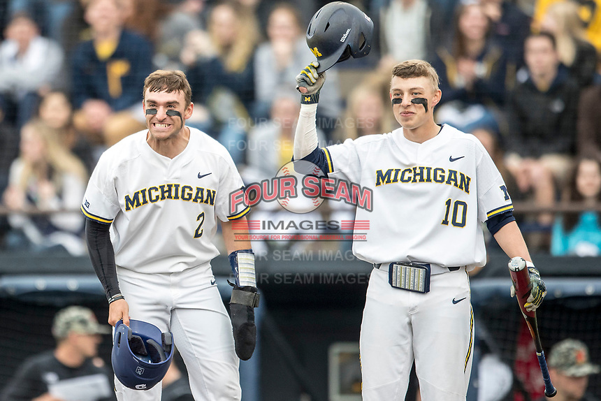 Michigan Wolverines outfielder Jonathan Engelmann (2) and teammate Blake Nelson (10) wait at the plate for Jesse Franklin (7) to arrive after his first inning home run against the Maryland Terrapins on April 13, 2018 in a Big Ten NCAA baseball game at Ray Fisher Stadium in Ann Arbor, Michigan. Michigan defeated Maryland 10-4. (Andrew Woolley/Four Seam Images)