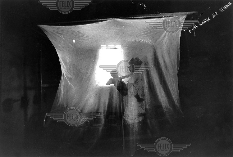 ©Giacomo Pirozzi/Panos Pictures..Zambia, Mother and protected by a mosquito net.