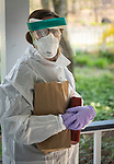 Public health nurse Lori Smittle from the Westchester County Health Department on a home visit to test for COVID-19 in Pleasantville, New York.<br /> <br /> Before entering the home to administer the tests, she stopped on the porch to put on head to toe protective garb.
