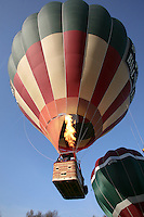 Blasts from the propane burners lift the balloon into the sky, British School of ballooning, Ebernoe, West Sussex.