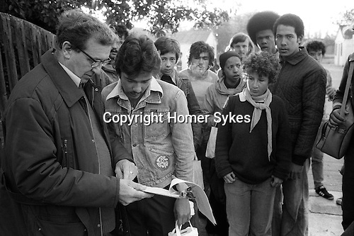 Foreign overseas students seasonal fruit picking Wisbech Cambridgeshire UK. Local farmer is checking names from a register of student pickers before they get on a lorry that takes them out to the apple orchard.