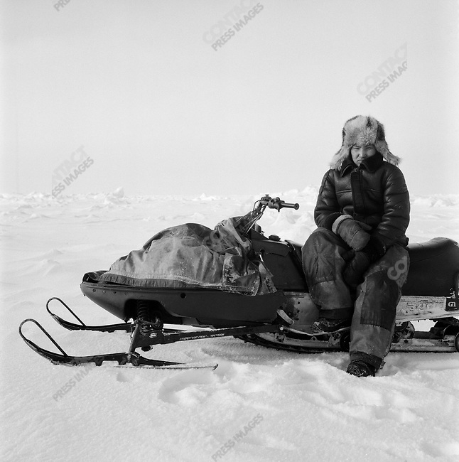 A hunter from the village of Vankarem (located on the Chukchi Sea) in the far north of Chukotka, waited on his snow mobile as other hunters went to look at the ice in search of seals. Chukotka Autonomous Okrug, Russia, April 2007...