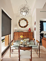 A Taraxacum 88 suspension light by Achille Castiglioni hangs above the glass dining table in the dining area of the open-plan living space