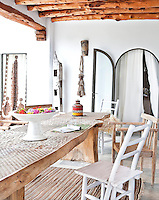 The shaded terrace is furnished with a spectacular carved wooden table and an assortment of chairs