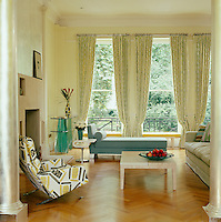 In this London living room tall floor-to-ceiling windows are framed in elegant green and white curtains echoing the tones in the garden beyond