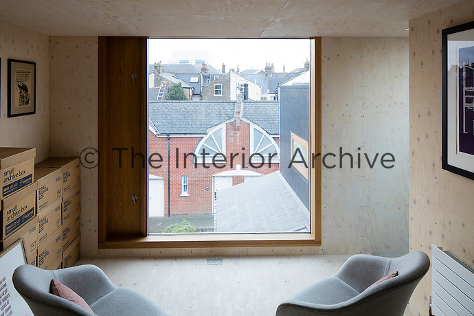 A Victorian home has been given a modernist aesthetic. The attic has been converted into a library and storage room and is clad in birch plywood. A mansard extension created space for a sitting room with a large picture window.