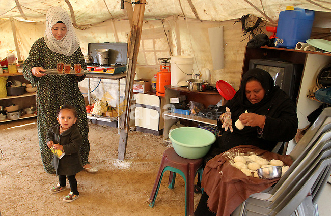 A Palestinian woman prepares the dough to bake bread at a tent near the ruins of her house which witnesses said were destroyed by Israel shelling during a 50-day conflict last summer, east of Khan Younis in the southern Gaza Strip January 27, 2015. The main U.N. aid agency in the Gaza Strip said on Tuesday a lack of international funding had forced it to suspend payments to tens of thousands of Palestinians for repairs to homes damaged in last summer's war. Robert Turner, Gaza director of operations for the United Nations Relief and Works Agency (UNRWA), said in a statement that UNRWA received only $135 million of the $720 million pledged by donors to its cash assistance program for 96,000 refugee families whose homes were damaged or destroyed in the 50-day conflict between the Hamas Islamist movement and Israel. Photo by Abed Rahim Khatib