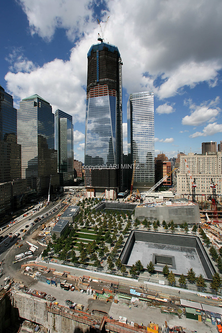 Tenth anniversary of 9/11.  Rebuilding at the World Trade Center site.  The view from south side of site shows L to R: World Financial Center, Goldman Sachs, 1 WTC, 7 WTC, and the postal building.   The 9/11 Memorial is situated around the footprints of the original towers.  The former Deutsche Bank site is in foreground, right.  Photo by Ari Mintz.  8/22/2011.