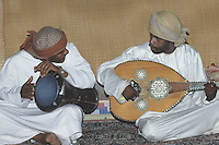 Wahiba Sands, Oman, Arabian Peninsula, Middle East - Omani Musicians, one playing the oud (the stringed instrument), the other a drum called the tabla.  Unlike the lute, the oud has no frets. Decorations on the oud are of ivory and mother-of-pearl.