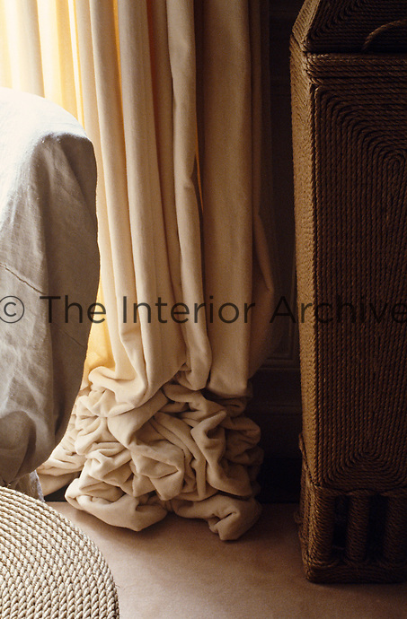 Detail of a crumpled cream curtain next to a piece of furniture made from rope