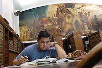 Law student Chris Ochoa studies in the Quarles &amp; Brady Reading Room of the Law Library, beneath the 37-foot long mural The Freeing of the Slaves, painted by John Steuart Curry from 1933 to 1942. Ochoa, who volunteers for the Innocence Project, says the mural reminds him of the value of freedom. The mural, originally intended for the Department of Justice headquarters in Washington DC, was refused due to the &quot;racial implications of the subject matter,&quot; according to Curry.<br /> <br /> Client: University of Wisconsin-Madison<br /> &copy; UW-Madison University Communications 608-262-0067<br /> Photo by: Michael Forster Rothbart<br /> Date:10/03    File#:   D100 digital camera frame 11326.