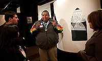 "Nikkia Owlchild of the Wanupum Indians explains the significance of the buried petroglyphs to students Central Washington University Museum of Culture and Environment  during an exhibit called ""Sacred Spaces"" in Ellensburg, Wash. on February 3, 2011.  When the Priest Rapids Dam was built in 1961 it flooded Whale Island which the Wanapum consider a holy place, burying the ancient petroglyphs.  This exhibit of rubbings made from the stone etchings was put together by Arlene Buck, Owlchild's aunt, now deceased. The student on the left is Joel Ratliff, an anthropology major at the university.  (photo credit Karen Ducey)"