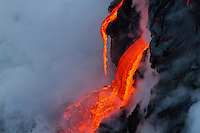 A lava drip hangs above a lower flow, surrounded by cooling lava and a billow of steam, Hawai'i Volcanoes National Park and the Kalapana border, Big Island.