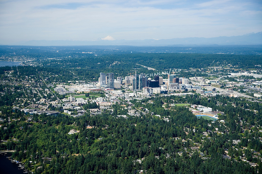 A late afternoon aerial photo of downtown Bellevue, a major Seattle Eastside suburb, looking north to snow-capped Mount Baker in the far distance.  Construction cranes belie the building boom that has happened in this suburban city during the first decade of the 21st century.