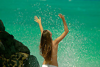 Young woman at beach playing with splashing ocean and rocks