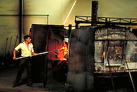Glassblower pulls glowing piece from oven. Tijuana, Mexico.
